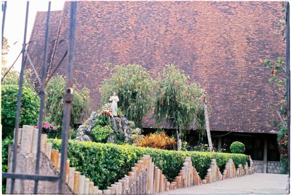 Đường dẫn vào nhà thờ tràn ngập những loài hoa nhỏ xinh. Mái công được xây bằng loại gạch màu cũ xưa theo hình nhà tháp, giống cấu trúc nhà rông của đồng bào Tây Nguyên.