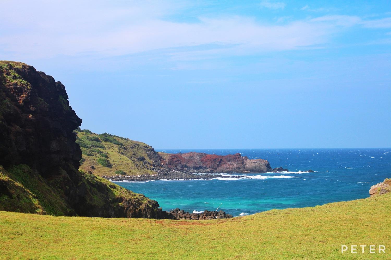 Từ bãi cỏ xanh rì nhìn ra biển, dọc bờ là những vách núi đá đen xen cỏ xanh.