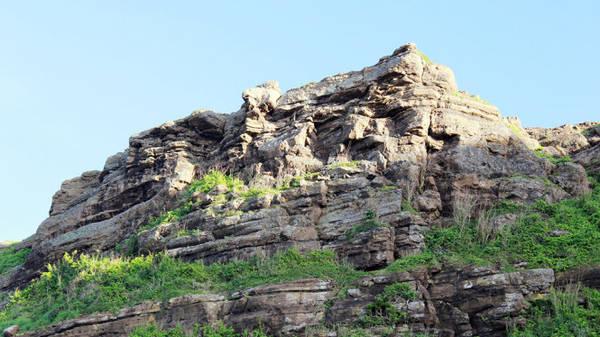 Một chóp núi bị quá trình phong hóa làm cho lồi lõm - Ảnh: Trần Mai