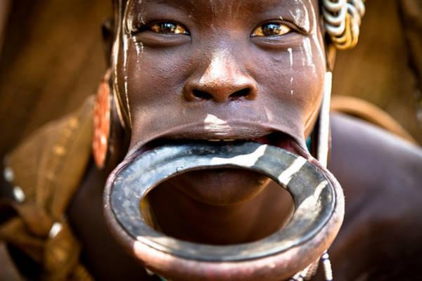 Bộ tộc Mursi, Ethiopia: Môi dưới của phụ nữ trong bộ tộc được tạo lỗ từ khi còn nhỏ, sau đó lồng một chiếc đĩa gốm vào. Kích cỡ đĩa tăng dần theo thời gian và đĩa càng lớn càng được coi trọng. Ảnh: Sosyal Bilimler.