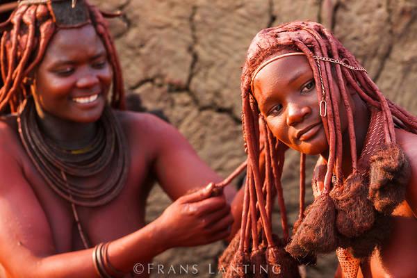 Bộ tộc Himba, Namibia: Phụ nữ của tộc Himba nổi tiếng với tóc và làn da ánh đỏ. Họ bôi otjize - một hỗn hợp gồm bơ, mỡ và đất đỏ - lên tóc và da hàng ngày. Nhiều người cho rằng otjize giúp tránh nắng và chống côn trùng, nhưng tộc Himba cho biết họ dùng chúng chỉ hoàn toàn vì lý do thẩm mỹ. Ảnh: Frans Lanting.