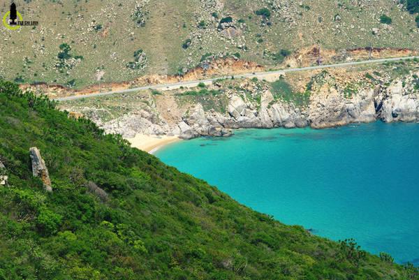 """Một bên xanh ngắt màu nước biển, một bên xanh mướt mắt cây rừng, tạo nên một """"con đường màu xanh"""" tuyệt đẹp. Một trong những điểm nhấn của đường DT702 là bạn sẽ vượt qua hàng loạt bãi biển hoang sơ trong xanh như ngọc, từ những bãi tắm vô danh, đến bãi Chuối, bãi Kinh, bãi Nước Ngọt..."""
