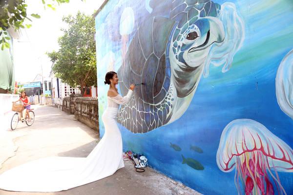 """Bích hoạ """"Nói Không Với Túi Ni Lông"""" của hoạ sĩ Trang. Sắp tới, Trang sẽ lên xe hoa. Cùng với mong muốn đóng góp công sức của mình cho dự án, Trang đã tình nguyện đến đảo vẽ đồng thời chụp ảnh cưới tại chính tác phẩm của mình. Ảnh: Nguyễn Hồng Minh"""
