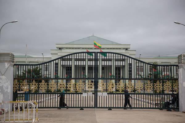 Binh lính canh gác đứng ngoài trụ sở của Đảng Liên minh Đoàn kết và Phát triển Myanmar. Tuy nhiên, công việc của họ có vẻ nhàn rỗi.