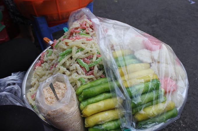 Bánh tằm Cổng chợ có gánh bánh tằm nhiều màu sắc. Miếng bánh dẻo dai lăn qua dừa bào nhuyễn tạo vị ngọt thơm. Chỉ với 5.000 đồng bạn sẽ được thưởng thức món ăn này.