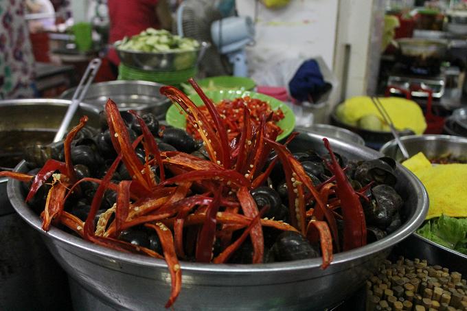 Ốc xào dừa Hàng Thu Hà trong chợ đắt khách nhất là món ốc xào dừa. Điểm thu hút của món ăn này là vị thơm của nước dừa hoà quyện trong vị dai của con ốc và vị cay của nước chấm. Giá mỗi dĩa ốc dao động từ 30.000 đồng, tùy loại lớn nhỏ.