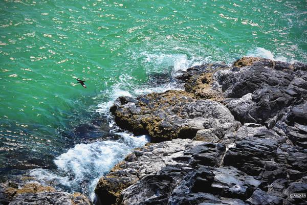 Ngay dưới chân, vách vực sâu dựng đứng với những khối đá đen trầm mặc, sóng tung bọt trắng xóa.