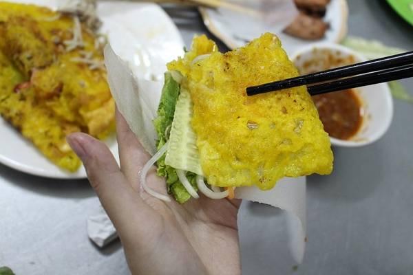 Bánh được dọn ra đĩa nóng hổi, cắt đôi miếng bánh cho dễ cuốn, bên cạnh là đĩa rau sống, đu đủ chua và dưa leo cuốn kèm bánh tráng mỏng.