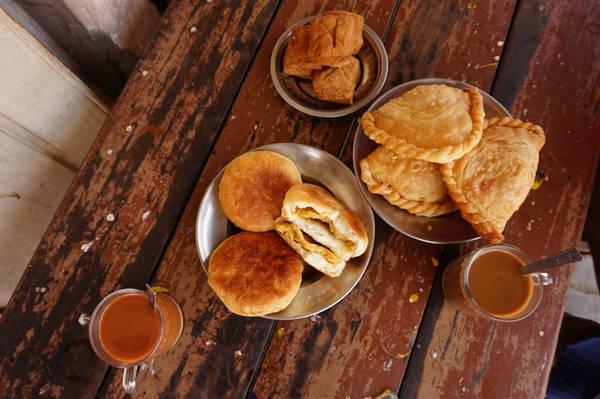 Các quán trà của người Ấn hoặc người theo đạo Hồi phục vụ nhiều món chịu ảnh hưởng từ ẩm thực của Đông Nam Á, như samosas hay poori (bánh mì rán giòn với cà ri khoai tây) hay bánh mì nướng như nanbya. Ảnh: WanderGuts.