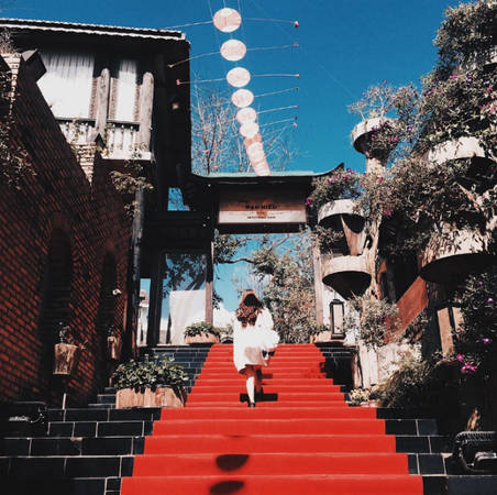 """Con dốc dài sơn đỏ, cổng gỗ đặc trưng, những căn nhà cổ mái ngói nép mình bên những tán hoa anh đào chắc chắn sẽ khiến bạn lầm tưởng đang ở xứ phù tang. Làng cổ Nhật Bản có tên gọi là XQ Đà Lạt Sử Quán mang kiến trúc đậm chất phương Đông, nằm trên con đường Mai Anh Đào """"ai ai cũng biết tên"""". Ảnh: Thùy An"""