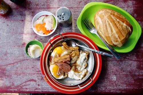 Đặc trưng của quán là món bánh mì chảo. Bên trong chảo là đủ thứ nguyên liệu như trứng gà ốp la, thịt nguội, xúc xích, chả cá, chả lụa... Tất cả đều được chiên nóng cháy cạnh cùng ít hành tây và dùng nóng với bánh mì. Nếu không thích dùng ốp la, bạn có thể gọi một phần thịt nguội thập cẩm riêng, rắc lên ít tiêu, nước tương, tương ớt. Giá trung bình một phần bánh mì ăn kèm trứng trên chảo là 40.000 - 45.000 đồng. Ảnh: Phong Vinh.