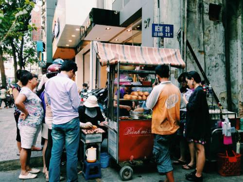 Bánh mì thịt nướng Nguyễn Trãi  Tầm 5-6h chiều, trong con hẻm nhỏ trên đường Nguyễn Trãi, xe hàng bán duy nhất món bánh mì thịt nướng đông khách vây quanh. Người bán nhanh tay nướng những viên thịt nướng trên bếp than nhỏ, rồi cho vào bánh cùng rau dưa, ớt. Hẻm không có chỗ để xe, có người phải gửi xe ở xa và đi bộ lại. Ảnh: Huỳnh Duyên.