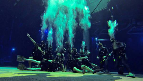 Trong số các nhân viên có 30 thợ lặn chuyên nghiệp trong hồ bơi mà khán giả sẽ không bao giờ nhìn thấy. Họ nắm giữ một trong những vai trò quan trọng nhất. Công việc của họ là định hướng và đưa mặt nạ thở dưới nước cho người biểu diễn. Họ đeo mặt nạ kín toàn bộ khuôn mặt, giúp họ nói chuyện được với các nghệ sĩ dưới nước. Ảnh: Dragone Entertainment.