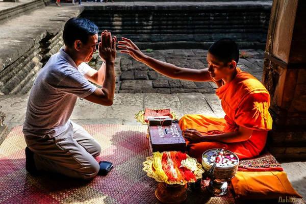 Một nghi lễ trong đền Angkor Wat - nghi lễ buộc chỉ cổ tay để xin may mắn, sức khỏe. Chỉ đỏ tượng trưng cho sự may mắn, chỉ vàng tượng trưng cho sức khoẻ.