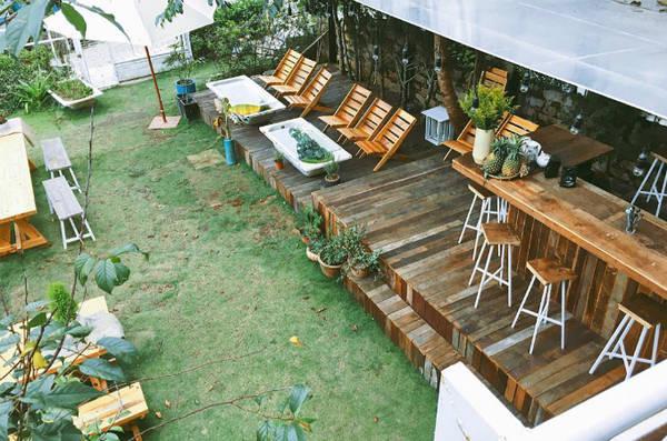 Quầy bar ngoài hiên, thảm cỏ xanh, bàn ghế gỗ, những chiếc ô trắng tạo nên một studio ngoài trời xinh xắn. Chỉ cần ngồi sưởi nắng trong không gian này cũng đủ khiến bạn khó quên. Ảnh: alazycatwanders