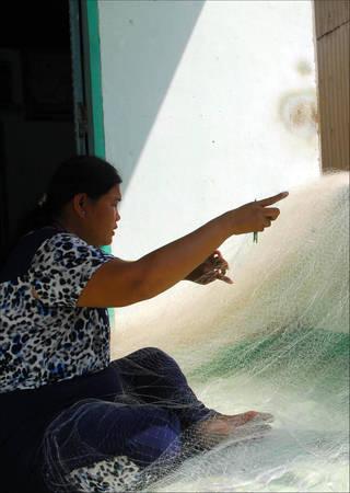 Một ngư dân đan tấm lưới mới để chuẩn bị cho chuyến đánh bắt thủy hải sản. Người dân nơi đây vô cùng chất phác, thân thiện và mến khách - điều dễ bắt gặp ở những làng chài. Ảnh: Lê Mạnh Linh.