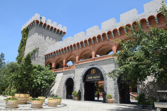 Nhìn từ phía ngoài, tòa lâu đài có kiến trúc như tường thành, tường xây bằng gạch đỏ và trắng, xung quanh bao bọc nhiều cây xanh.