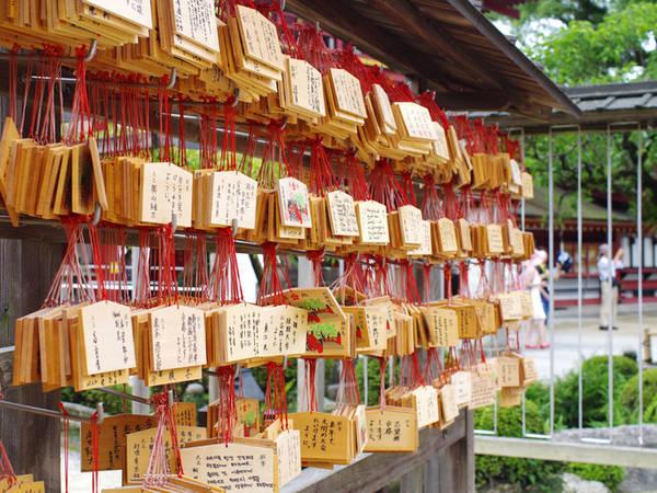 Đền Dazaifu Đền thờ Sugawara no Michizan, người được tôn sùng như một vị thần của học vấn, sự thành thật và trừ tai họa, do đó hàng năm có khoảng 7 triệu lượt người đến viếng đền. Đây là một địa điểm thu hút nhiều sĩ tử đến cầu nguyện vào mỗi mùa thi. Ngoài ra, nơi làm đền Dazaifu từng là vùng đất giao lưu văn hóa giữa các nước châu Á. Hiện tại ngôi đền này nổi tiếng là có nhiều khách nước ngoài tới tham quan, chủ yếu là từ khu vực châu Á. Cổng đền có trâu đá được nhiều sĩ tử và khách tới chạm vào để lấy may. Bên trong đền có khu vực bốc thẻ, ghi lời ước nguyện... Ảnh: Hương Chi.