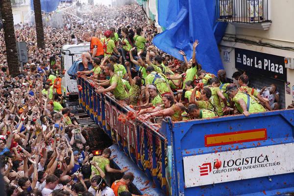 Những người trên xe hất cà chua xuống đường, hàng chục nghìn du khách sẽ cùng tham gia đại chiến, ném cà chua vào nhau trong tiếng reo hò, gào thét vui vẻ. Ảnh: Alberto Saiz / AP.