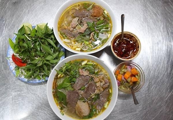 Tô bún bò nóng hổi bên cạnh đĩa rau sống, ăn kèm với hành tím ngâm, rau thơm và một ít sa tế mới đầy đủ hương vị.
