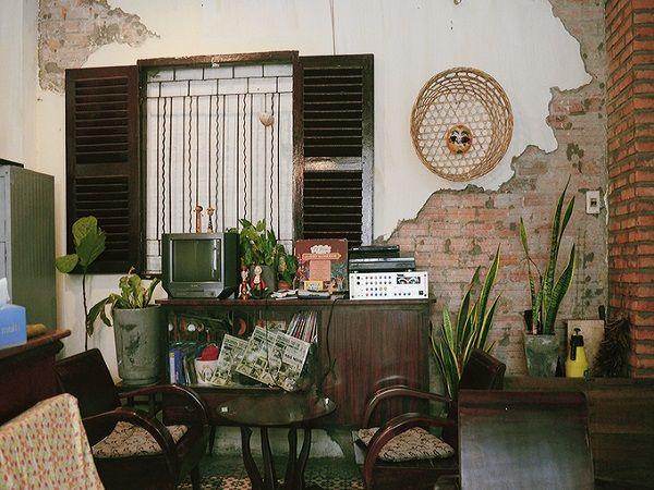 Không lẫn vào không khí nhộn nhịp tại trung tâm Sài Gòn, quán cà phê Nhà Mình nằm khuất trong một con đường nhỏ ở quận 3. Những bộ bàn ghế gỗ được kết hợp hài hòa với đồ dùng xưa cũ, thêm ánh sáng và gió trời tự nhiên cùng vài mảng xanh của cây cối... tất cả khiến không gian quán trở nên gần gũi và dễ chịu.