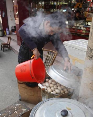 Người bán vớt trứng ra, gõ cho vỏ rạn rồi lại bỏ vào nồi ninh trong một ngày. Trong quá trình ninh, nước tiểu được thêm vào liên tục, cùng một số thảo dược. Ảnh: Ibtimes.