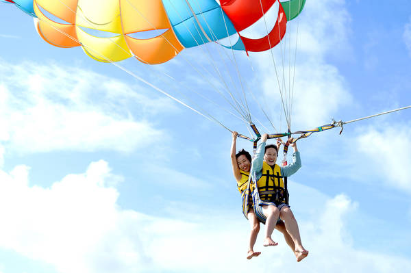 """Ngày thứ 4 của hành trình, đoàn khảo sát du lịch đi thưởng ngoạn trò chơi dù lượn trên không. Khác với nhiều nơi bay dù thường cho khách """"cất cánh"""" ngay tại bãi cát, tại đây từng nhóm khách được ca nô chở ra ngoài xa, cách bãi biển chừng 2 km để tham gia."""