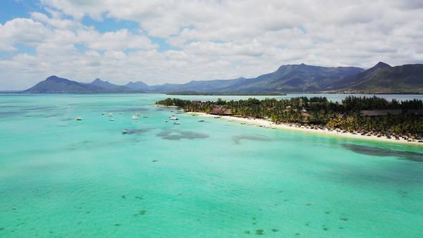 Rặng san hô lớn thứ 3 thế giới bao quanh hòn đảo chặn các con sóng cách bờ 2 km tạo nên bãi biển phẳng lặng tuyệt đẹp.