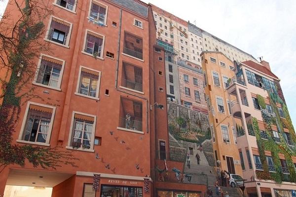 """Một trong những dự án nổi tiếng nhất của họ là bức tranh rộng hơn 1.200 m2 có tên """"Mur des Canuts"""" nằm ở quận Croix-Rousse. Bức tranh mô tả một cầu thang lớn ở giữa với các tòa nhà hai bên và đằng xa. Ở dưới cùng tranh là một số cửa hàng và một ngân hàng."""