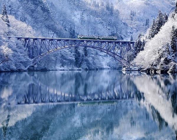 """Tadami, Aizu, Fukushima  Đây là một ngôi làng nằm ở vùng núi có rất nhiều góc cho du khách ngắm """"đã"""" mắt. Bên cạnh các ngọn núi, hồ nước, làng còn có hai dòng sông Ina và Tadami chảy qua. Một cây cầu đường sắt cũng rất nổi tiếng có tên Tadami line. Tuyết rơi ở Aizu thuộc vào top nhiều nhất ở Nhật vì thế các khu rừng, dốc núi đều sẽ phủ một lớp tuyết dày tạo cảnh tượng đẹp như cõi tiên. Ảnh: Hide Ktg."""