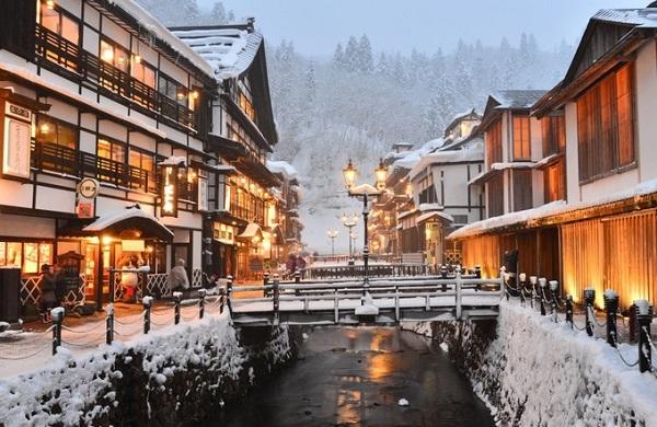 Ginzan Onsen, Yamagata  Từng là một nơi nổi tiếng với nghề khai thác bạc, Ginzan Onsen hiện là một điểm đến nghỉ dưỡng nổi tiếng ở Yamagata, thuộc vùng Tohoku. Vào mùa đông những ngôi nhà gỗ truyền thống ở đây nổi bật với ánh đèn vàng, mái ngói phủ đầy tuyết, và không khí Giáng sinh ngập tràn đường phố. Ảnh: jnto.