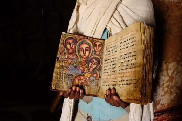 Một linh mục giới thiệu cuốn kinh thánh cổ làm bằng da dê còn lưu giữ trong nhà thờ - Ảnh: New Faces New Places