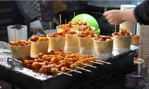 Mua sắm, ăn uống ở Myeongdong  Vào buổi sáng Myeongdong là một khu phố nhộn nhịp người mua bán, khách du lịch ăn uống. Đến buổi tối, Myeongdong biến thành một khu chợ đêm với các con phố trải đầy những hàng quán, sạp bán đủ loại đồ ăn, đồ lưu niệm, túi xách... Ảnh: JencookKorean.