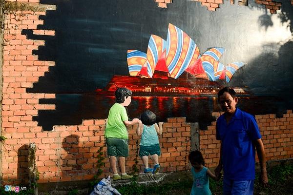 Buổi chiều, ông Trần Thanh Sơn dắt cháu tham quan những bức tranh vẽ trong làng.