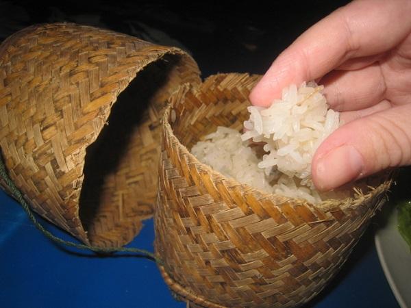 Khao Niaw (Xôi) nấu từ gạo dẻo, màu trắng ngà là món không thể thiếu trong tất cả các bữa ăn ở đây. Xôi được đựng trong một giỏ nhỏ đan bằng tre đơn giản, mộc mạc. Ăn đúng kiểu Lào là phải dùng tay nén thành viên tròn rồi mới cho vào miệng - Ảnh: mmmgoodfood