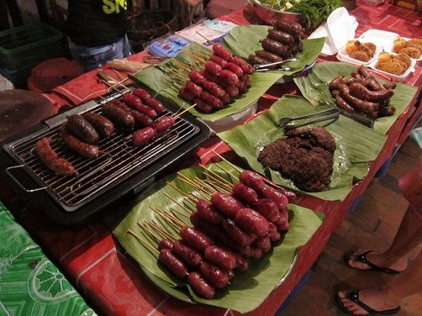 Xúc xích Lào khá phổ biến trong các khu chợ đêm, thường được làm từ thịt mỡ lợn ướp với thảo mộc và ớt, rồi xông khói cho hương vị lạ lẫm. Bên cạnh đó món xúc xích cay làm từ thịt trâu nước cũng rất hút khách - Ảnh: Isriya Paireepairit.