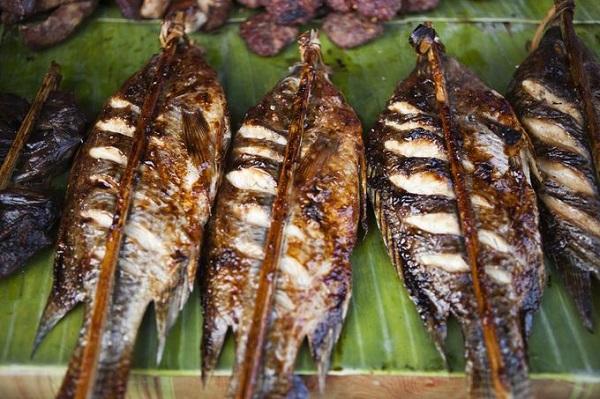Lào không có biển nên thường sử dụng cá sông để nướng, gọi là Ping Pa. Cá sông thịt ngọt hơn, ướp lá chanh, rau mùi... nướng đến vàng da dậy mùi thơm hấp dẫn thực khách - Ảnh: Tim Gerard Baker