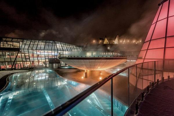 Đêm xuống, khung cảnh mờ ảo sương khói và hiệu ứng từ đèn điện khiến hồ bơi trông như một viên ngọc bích lấp lánh giữa không gian yên tĩnh.
