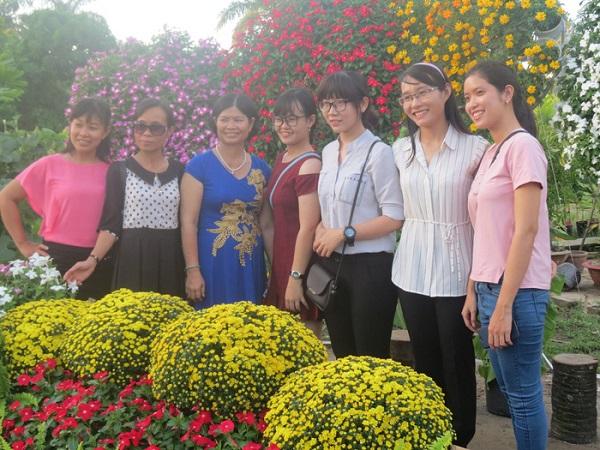 Khách du lịch chụp ảnh bên tiểu cảnh hoa trong vườn hoa thuộc Làng hoa Sa Đéc