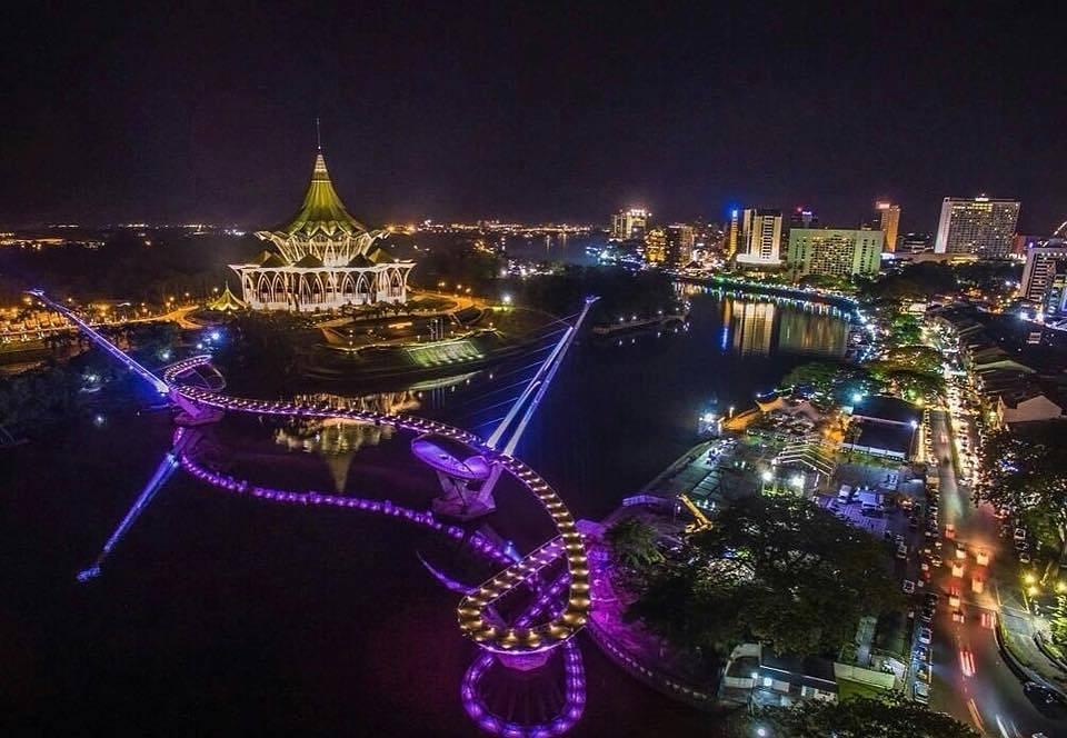 Sự đông đúc của Kuching tập trung nhiều ở phía bờ nam sông Sarawak, đây cũng là nơi Hoa kiều sống tập trung với nhau, với các kiến trúc quan trọng đều được sơn phủ màu xanh da trời. Phía bờ Bắc ít nhộn nhịp hơn, nổi bật với kiến trúc xanh lá, là nơi chủ yếu người Malaysia và thổ dân Bumi sinh sống. Bạn có thể đi sampan (taxi trên sông) để ngắm nhìn toàn cảnh thành phố. Nổi bật là cầu bộ hành Golden Anniversary Bridge dài 330m. Cầu vừa khánh thành năm 2017, được coi như biểu tượng mới của Kuching với những đường uốn lượn độc đáo bắc qua sông Sarawak.