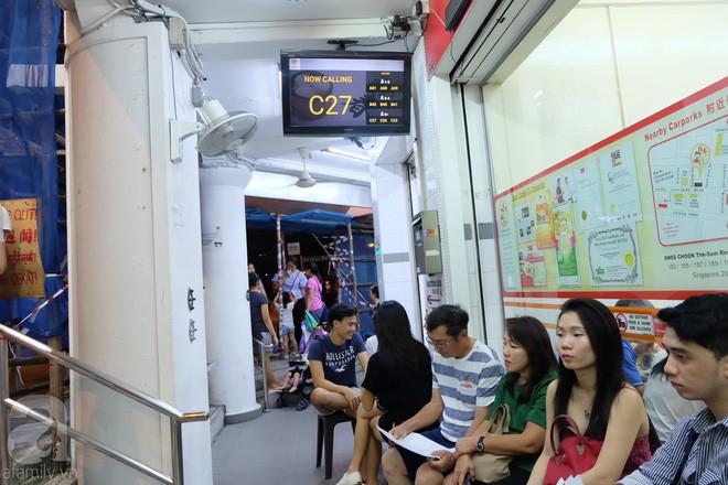 Máy lấy số và bảng điện tử bên ngoài hiển thị tình hình khách ăn trong quán và bàn trống. (Ảnh BB)