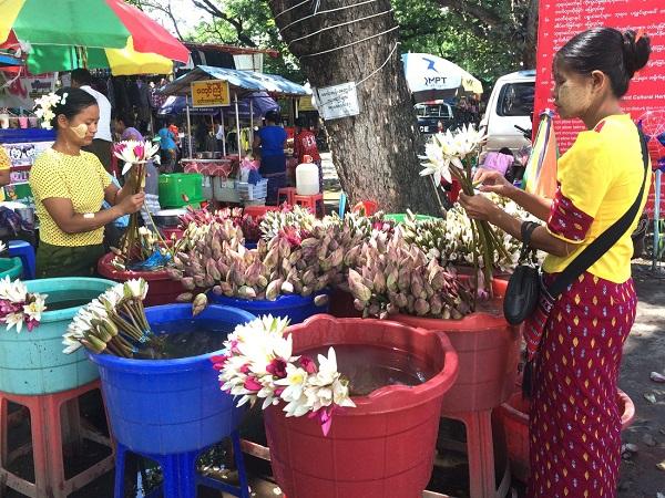 Trước cổng chùa, những người phụ nữ Myanmar chăm chút từng cánh hoa để bán cho khách viếng chùa, trên má ửng màu của nắng, điểm xuyến họa tiết của bột dưỡng da Thanaka - Ảnh: Bông Mai