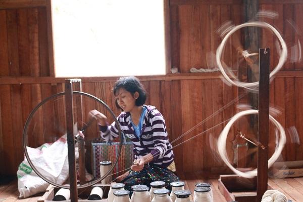 Thiếu nữ Myanmar quay những sợi tơ được làm bằng sen - Ảnh: Bông Mai
