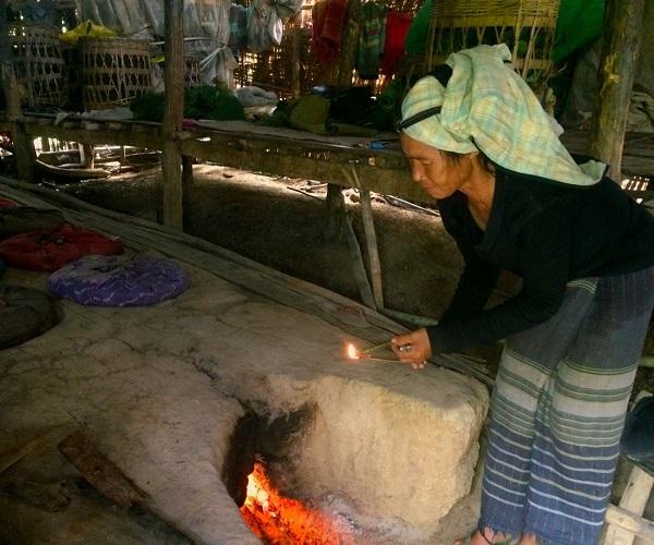 Buổi trưa trên đồi ở vùng đất Shan, Myanmar, người phụ nữ Myanmar đốt điếu thuốc lá do chính mình làm ra trên ngọn lửa đang sử dụng để hong khô lá cây thuốc lá - Ảnh: Bông Mai
