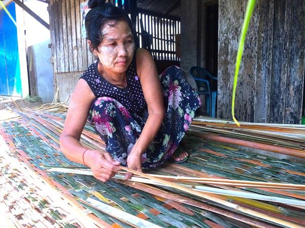 Bên bến sông, người phụ nữ Myanmar mãi miết đan vách bằng tre - Ảnh: Bông Mai