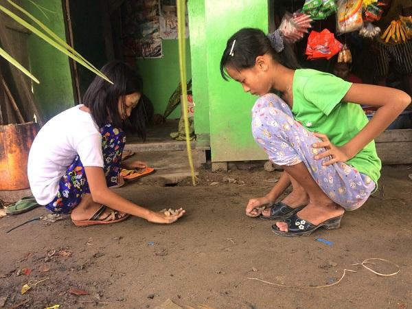 Kế bên người phụ nữ đan vách tre là hai cô bé chơi thảy đá khéo léo - Ảnh: Bông Mai