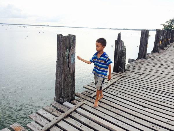 Tại Mandalay, trên cầu làm gỗ tếch dài và lâu đời nhất thế giới bắc qua sông Taungthaman, một cậu bé chăm chú ngắm nhìn phía dưới cầu - Ảnh: Bông Mai