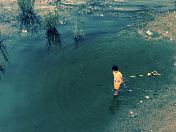 Dưới cầu gỗ tếch, một đứa trẻ mãi miết kéo đồ chơi làm bằng sợi dây nhựa và những mảnh gỗ không dùng nữa - Ảnh: Bông Mai