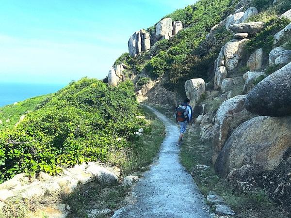 Cái nắng gió của xã đảo Bích Đầm vơi đi phần nào khi một bên là vách đá hùng vĩ, một bên là biển xanh sóng vỗ - Ảnh: Bông Mai