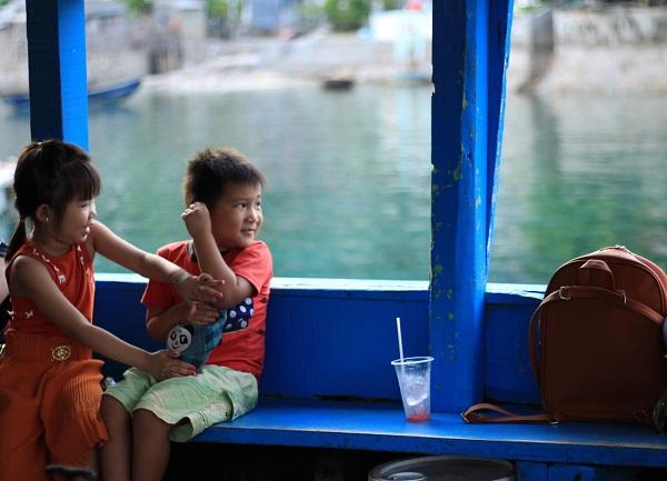 Phút nô đùa hồn nhiên của những đứa trẻ cùng mẹ rời đảo vào sáng tinh mơ để ra đất liền mua sắm vài món đồ cần thiết - Ảnh: Bông Mai